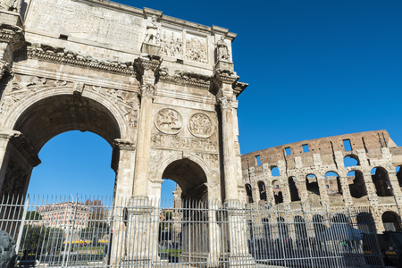 Arch of triumph known as Arch of Constantine with the coliseum in the background in Rome, Italy