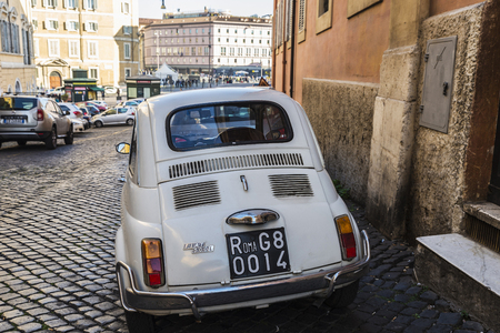Rome, Italy - January 1, 2017: White Fiat 500 car parked on a historic street in Rome, Italy