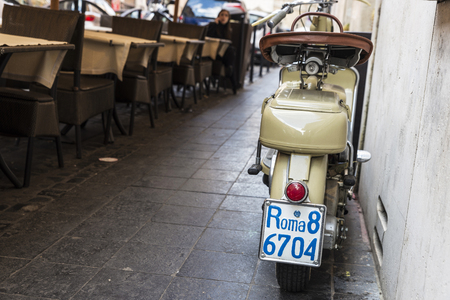 Rome, Italy - January 2, 2017: Classic motorcycle parked on the sidewalk in front of a bar with the license plate of Rome, Italy Editorial