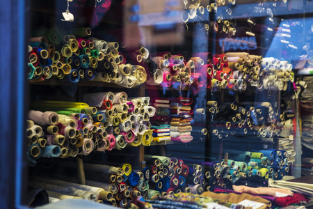 Rolls of cloth for sale in a fabric shop in the historic center of Rome, Italy Stock Photo