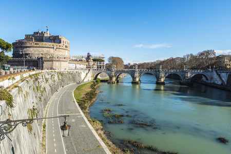 View of the castle of Sant Angelo and the bridge of Sant Angelo with people walking around in Rome, Italy