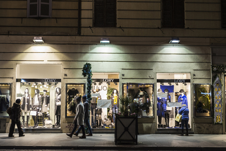 illuminated: Rome, Italy - January 4, 2017: People strolling down a street with fashionable Lory brand clothing stores  at night in Rome, Italy