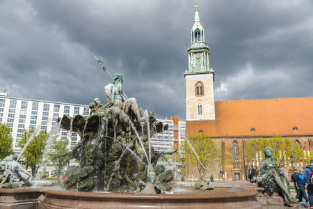 Berlin, Germany - April 13, 2017: People walking around Neptune fountain (Neptunbrunnen) with the St Mary church (Marienkirche) in the background in Alexanderplatz square, Berlin, Germany