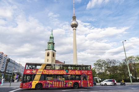 Berlin, Germany - April 13, 2017: Tour bus with St Mary church (Marienkirche) and telecommunications tower with people walking in Alexanderplatz square in Berlin, Germany
