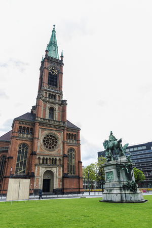windows and doors: St John church (Johanneskirche) of Historicism style with people walking and the statue of Kaiser Wilhelm I in front in Dusseldorf, Germany