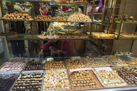 Cardona, Spain - October 30, 2016: Assortment of panellets in the shop window of a pastry shop with customers choosing. Panellet are traditional desserts of All Saints holiday, known as Castanyada in Cardona, Catalonia, Spain