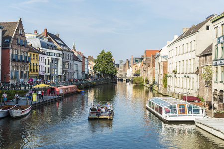 Ghent, Belgium - August 28, 2017: Tourists sailing with a boat between old houses along the Leie river in Ghent, Belgium