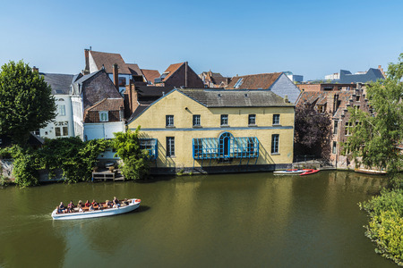 Ghent, Belgium - August 29, 2017: Old houses along the Leie river with people sailing in a boat in the medieval city of Ghent, Belgium