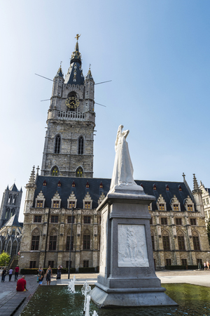 Ghent, Belgium - August 29, 2017: Belfry of Ghent, bell tower, next to the Cloth Hall with people walking in the medieval city of Ghent, Belgium