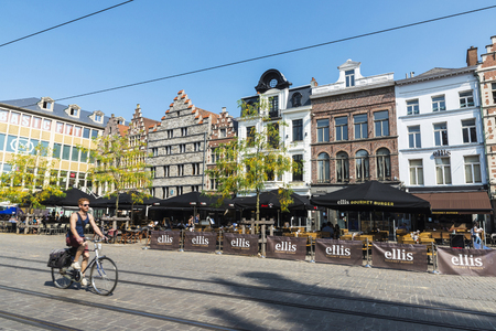 Ghent, Belgium - August 29, 2017: Young man on bicycle circulating and people walking in an old historic center of the medieval city of Ghent, Belgium