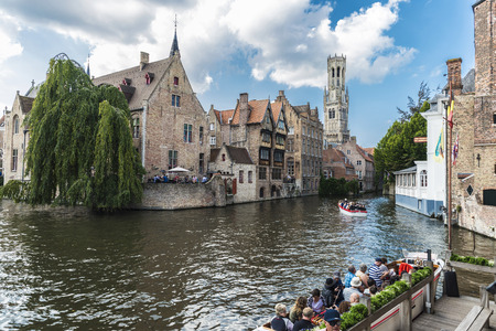 Bruges, Belgium, - August 31, 2017: Rozenhoedkaai or Rosary Dock with people sailing on a boat in the medieval city of Bruges, Belgium