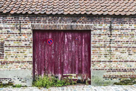 Wooden door of an old abandoned building in an old historic center of the medieval city of Bruges, Belgium Standard-Bild