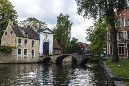 Convent of Sancta Elisabeth Sauve Garde along the river with white swans swimming in the medieval city of Bruges, Belgium Stock Photo
