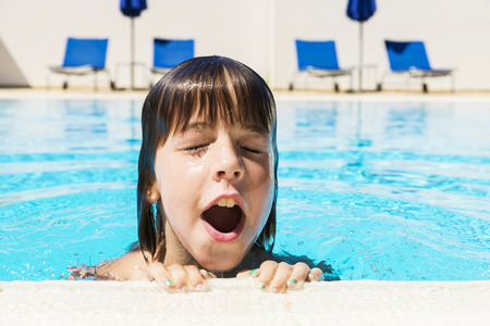 Little girl with his mouth open and his eyes closed coming out of the water in an outdoor pool Banque d'images