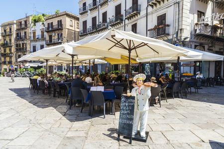 Palermo, Italy - August 10, 2017: Terrace of a restaurant bar with people around in the old town of Palermo in Sicily, Italy