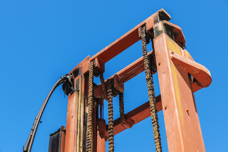 Chain gear of an old forklift in a construction site against the blue sky in the south of Sicily, Italy