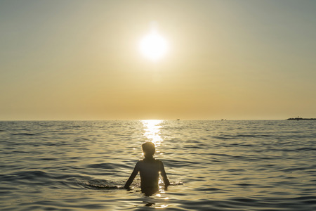 Teenager boy bathing in the sea at sunset in summer in Sicily, Italy Stock Photo