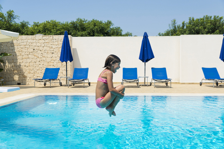 Smiling little girl jumping in pump in a swimming pool of a resort hotel in summer in Sicily, Italy
