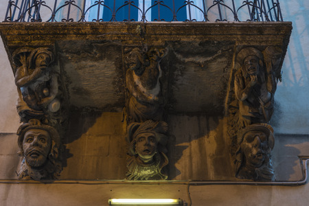 Sculptures of human figures on the cornice of a balcony in the historic village of Ragusa in Sicily, Italy