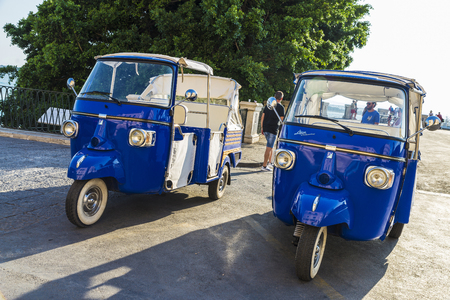 Siracusa, Italy - August 17, 2017: Two blue tricycles of the Piaggio brand that make tourist circuits with people around parked on a street in the old town of Siracusa in Sicily, Italy Editorial