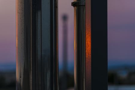 Abstraction of a sunset reflected on two metal columns in summer
