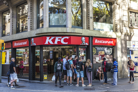 Barcelona, Spain - September 20, 2017: Young tourists in front of a Kentucky Fried Chicken (KFC) in Les Rambles of Barcelona, Catalonia, Spain Editorial