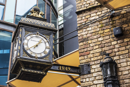 London, England UK  - December 31, 2017: Old classic wooden clock with Roman numerals hanging on the wall in Camden Lock Market or Camden Town in London, England, United Kingdom Redactioneel