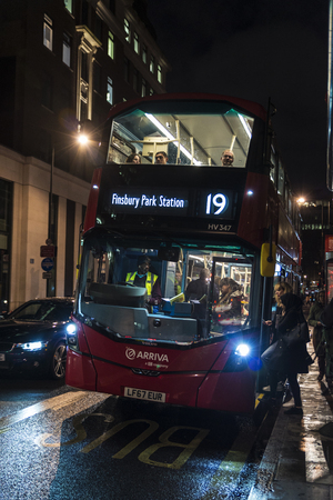 London, England UK  - December 31, 2017: Women of different races getting on a bus at a bus stop at night in London, England, United Kingdom
