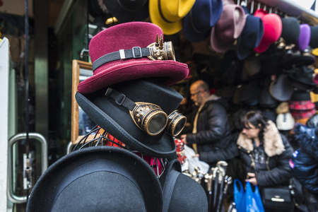 London, United Kingdom  - December 31, 2017: Hats and Gothic black sunglasses with diffracted lens or Kaleidoscope in a fashion shop of Camden Lock Market or Camden Town with people around in London, England, United Kingdom