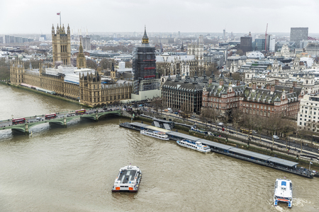 Overview of The Palace of Westminster and the Thames river with boats sailing and moored on the River Thames in the city of London, England, United Kingdom Redakční