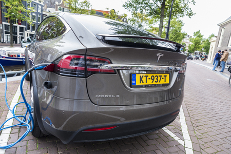 Amsterdam, Holland - September 8, 2018: Electric car Tesla Model X plugged into a power station on a street in Amsterdam, Holland