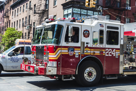 New York City, USA - July 26, 2018: Fire truck circulating on a street with people around in New York City, USA