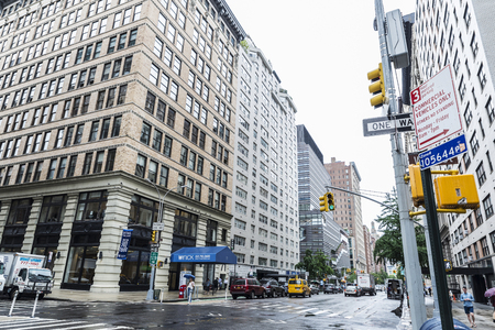 New York City, USA - July 25, 2018: Fifth Avenue in a rainy day with modern new skyscrapers, traffic and people walking in New York City, USA