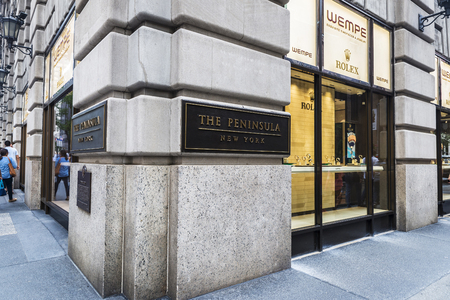 New York City, USA - July 28, 2018: Display of a luxury Wempe jewelry in Fifth Avenue (5th Avenue) with people around and an ad by The Peninsula Hotel and Rolex in Manhattan in New York City, USA Editorial