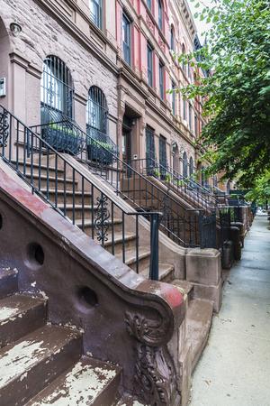 Old typical houses in the Harlem neighborhood in Manhattan, New York City, USA 免版税图像