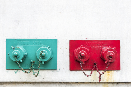Four fire hydrants in a wall in red and green in Manhattan in New York City, USA