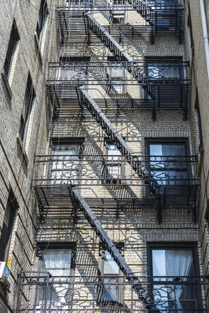 Old typical houses with its emergency stairs in the Harlem neighborhood in Manhattan, New York City, USA Editöryel