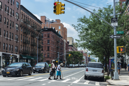 New York City, USA - July 28, 2018: Two old black women with a walking stick crossing a traffic light by crosswalk in Harlem, Manhattan, New York City, USA