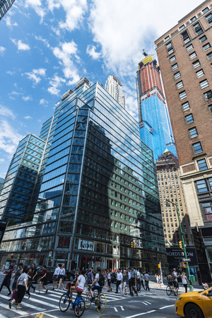 New York City, USA - July 28, 2018: 8th Avenue (Eight Avenue) with its modern skyscrapers and a taxi and people around in Manhattan, New York City, USA