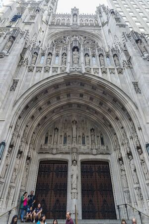 New York City, USA - July 28, 2018: Facade of The Saint Thomas Church on Fifth Avenue (5th Avenue) with people around in Midtown Manhattan, New York City, USA
