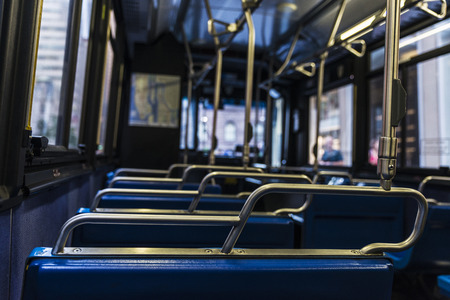 Empty blue seats with its metal handles inside a bus in Manhattan, New York City, USA Stock Photo