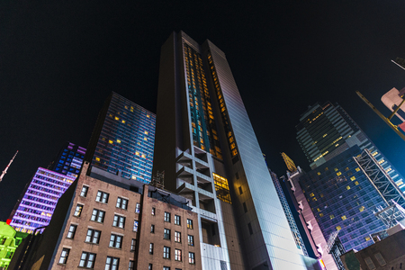 Facade of modern skyscrapers an old buildings illuminated with different colors at night in Manhattan, New York City, USA Redakční