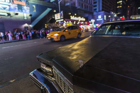 New York City, USA - July 30, 2018: Old classic black american car parked at night on Seventh Avenue (7th Avenue) next a taxi with people around in Manhattan in New York City, USA