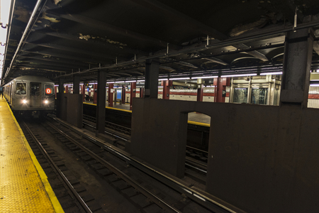 Train car in motion with its driver and people waiting in a subway station of New York City, USA