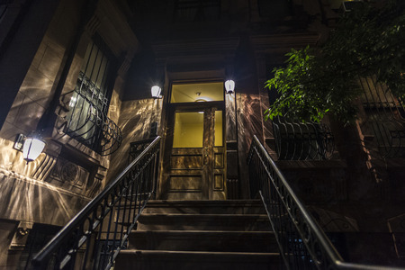Entrance of an old typical house at night in the Harlem neighborhood in Manhattan, New York City, USA