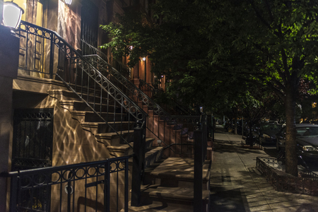 Old typical houses at night in the Harlem neighborhood in Manhattan, New York City, USA