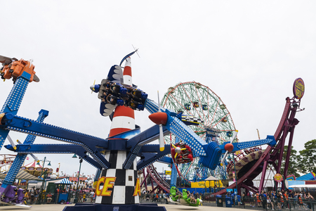 New York City, USA - July 30, 2018: Luna Park amusement park on summer with people in the rotating attraction that goes around in Coney Island Beach, Brooklyn, New York City, USA