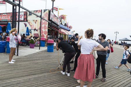 New York City, USA - July 30, 2018: Photographer photographs a fashion model girl at the entrance of the Luna Park amusement park on summer with people around in Coney Island Beach, Brooklyn, New York City, USA Editoriali