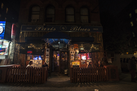 New York City, USA - August 2, 2018: Facade of the bar called Paris Blues Harlem with people having a drink on a terrace at night in Harlem, Manhattan, New York City, USA
