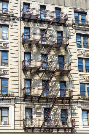 Old typical apartment buildings with its fire escape in the Harlem neighborhood in Manhattan, New York City, USA